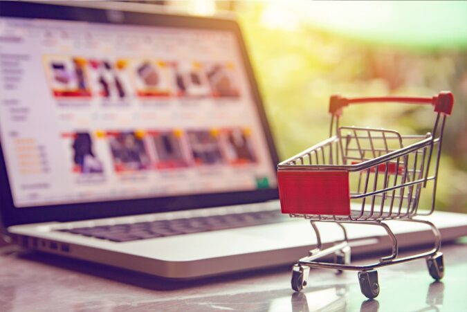 Shopping cart in front of laptop with ecommerce website on screen